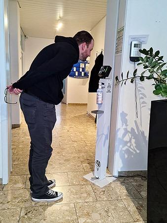 Eine Person misst am iseTOWER der isepos GmbH seine Körpertemperatur